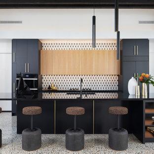 Einzeilige, Große Retro Wohnküche mit flächenbündigen Schrankfronten, schwarzen Schränken, bunter Rückwand, Rückwand aus Steinfliesen, schwarzen Elektrogeräten, Terrazzo-Boden, Kücheninsel und schwarzer Arbeitsplatte in Los Angeles
