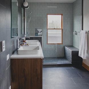 Imagen de cuarto de baño principal, tradicional renovado, de tamaño medio, con paredes blancas, suelo de baldosas de porcelana, armarios con paneles lisos, ducha abierta, sanitario de una pieza, baldosas y/o azulejos grises, baldosas y/o azulejos de porcelana, lavabo integrado, encimera de cuarzo compacto y puertas de armario de madera oscura