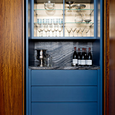 Example of a mid-sized trendy single-wall medium tone wood floor and brown floor dry bar design in Toronto with flat-panel cabinets, blue cabinets, granite countertops, multicolored backsplash, granite backsplash and multicolored countertops