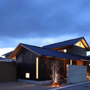 広いアジアンスタイルのおしゃれなLDK (ベージュの壁、塗装フローリング、薪ストーブ、石材の暖炉まわり、ベージュの床、表し梁、ベージュの天井) の写真