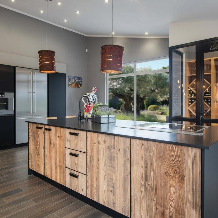 Les portes en sapin sont fabriquées à partir de planches de vieux bois récupéré en montagne, serties dans un cadre acier laqué noir mat ; au fond de la pièce, la partie réfrigérateur / fours est intég