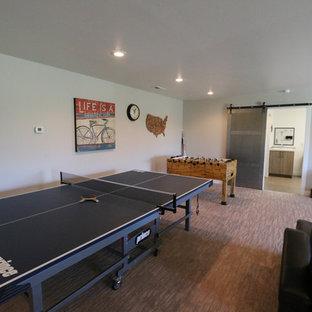 Aménagement d'une salle de séjour industrielle de taille moyenne avec salle de jeu, un mur beige, moquette, une cheminée d'angle, un manteau de cheminée en béton et un téléviseur fixé au mur.