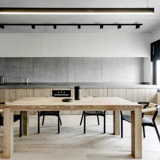 На фото: линейная кухня в современном стиле с обеденным столом, плоскими фасадами, светлыми деревянными фасадами, серым фартуком, черной техникой, светлым паркетным полом, бежевым полом и серой столешницей без острова с