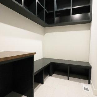Medelhavsstil inredning av en tvättstuga enbart för tvätt, med svarta skåp, träbänkskiva, vita väggar, klinkergolv i porslin, en tvättmaskin och torktumlare bredvid varandra och vitt golv