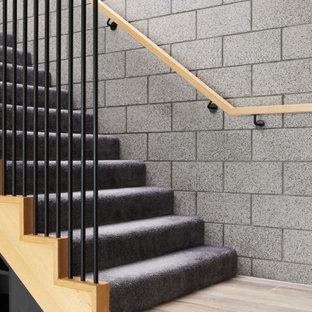 Idée de décoration pour un escalier design en L de taille moyenne avec des marches en moquette, des contremarches en moquette, un garde-corps en bois et un mur en parement de brique.