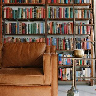 Immagine di un piccolo soggiorno industriale stile loft con libreria, pareti bianche, pavimento in cemento, nessun camino, TV nascosta e pavimento bianco