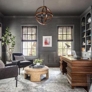 Modern inredning av ett mellanstort hemmabibliotek, med grå väggar, mörkt trägolv, en standard öppen spis, en spiselkrans i sten och ett fristående skrivbord