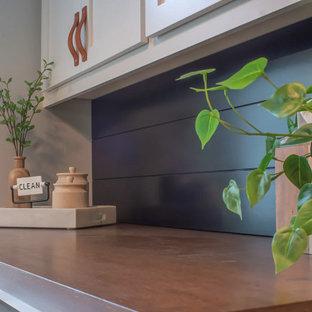 Idée de décoration pour une buanderie tradition de taille moyenne avec un évier utilitaire, un placard à porte shaker, des portes de placard blanches, un plan de travail en bois, une crédence en ardoise, un sol en ardoise, des machines côte à côte, un sol noir et un plan de travail marron.