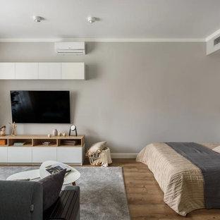 Ispirazione per un home theatre scandinavo di medie dimensioni e chiuso con pareti grigie, pavimento in laminato, TV a parete e pavimento marrone