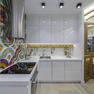 Создайте стильный интерьер: угловая кухня в стиле фьюжн с обеденным столом, накладной раковиной, плоскими фасадами, белыми фасадами, разноцветным фартуком и черной техникой без острова - последний тренд