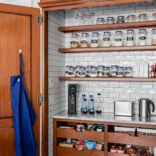 Amerikansk inredning av ett avskilt, stort grå grått u-kök, med en rustik diskho, skåp i shakerstil, grå skåp, bänkskiva i kvartsit, vitt stänkskydd, stänkskydd i keramik, integrerade vitvaror, mellanmörkt trägolv, en köksö och brunt golv