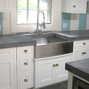This is an example of a transitional kitchen in Orlando with a farmhouse sink, beaded inset cabinets, white cabinets, concrete benchtops, stainless steel appliances and with island.