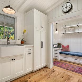 Idéer för stora funkis u-formade vitt tvättstugor enbart för tvätt, med en rustik diskho, skåp i shakerstil, vita skåp, marmorbänkskiva, vitt stänkskydd, stänkskydd i trä, vita väggar, ljust trägolv och en tvättmaskin och torktumlare bredvid varandra