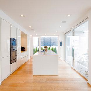 Offene, Einzeilige, Große Moderne Küchenbar mit Einbauwaschbecken, flächenbündigen Schrankfronten, weißen Schränken, Quarzit-Arbeitsplatte, Küchenrückwand in Grau, schwarzen Elektrogeräten, braunem Holzboden, Kücheninsel, braunem Boden und beiger Arbeitsplatte in Düsseldorf