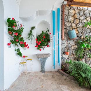Foto di un patio o portico mediterraneo di medie dimensioni e davanti casa con pavimentazioni in pietra naturale e una pergola