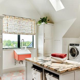 Пример оригинального дизайна: большая отдельная прачечная в стиле кантри с хозяйственной раковиной, фасадами с филенкой типа жалюзи, белыми стенами, со стиральной и сушильной машиной рядом, разноцветной столешницей и сводчатым потолком