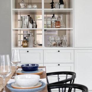 Immagine di una grande sala da pranzo aperta verso il soggiorno stile marinaro con pareti bianche, parquet chiaro, pavimento beige e soffitto in perlinato