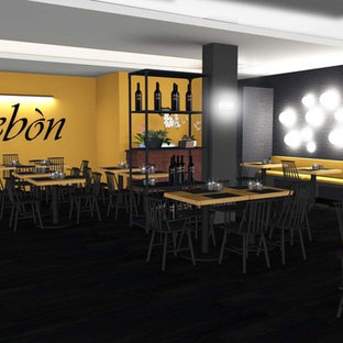 Foto di una sala da pranzo aperta verso il soggiorno industriale di medie dimensioni con pavimento in laminato, pavimento nero e pareti nere