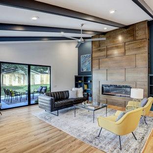 ヒューストンの広いミッドセンチュリースタイルのおしゃれなリビング (淡色無垢フローリング、横長型暖炉、木材の暖炉まわり、壁掛け型テレビ、表し梁) の写真