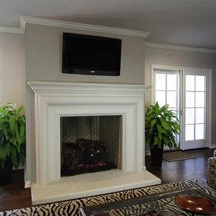 Ejemplo de sala de estar con rincón musical abierta, de estilo de casa de campo, de tamaño medio, con paredes grises, suelo de madera en tonos medios, chimenea tradicional, marco de chimenea de piedra y televisor independiente