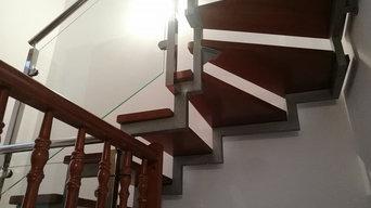 Escalera con peldaños en madera y barandilla inox con cristal