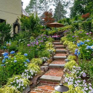 Photo of a huge traditional partial sun hillside brick landscaping in New York.