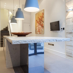 Large contemporary eat-in kitchen in London with an integrated sink, dark wood cabinets, limestone benchtops, white splashback, glass sheet splashback, stainless steel appliances and with island.