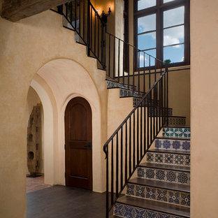 Imagen de escalera mediterránea con escalones de madera y contrahuellas con baldosas y/o azulejos