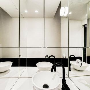 Ispirazione per un bagno di servizio minimal di medie dimensioni con ante lisce, ante nere, WC sospeso, piastrelle bianche, piastrelle a specchio, pareti nere, pavimento in cementine, lavabo a bacinella, top in quarzite, pavimento nero e top bianco