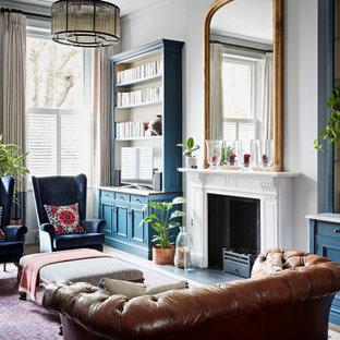 Großes Klassisches Wohnzimmer mit grauer Wandfarbe, dunklem Holzboden, Kamin, Kaminumrandung aus Stein, Eck-TV und braunem Boden in London
