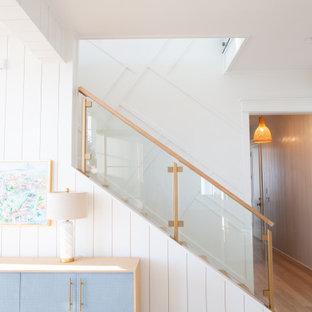 На фото: большая прямая лестница в морском стиле с деревянными ступенями, деревянными подступенками, стеклянными перилами и стенами из вагонки с