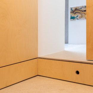 Inredning av en 60 tals liten garderob för könsneutrala, med släta luckor, skåp i ljust trä, klinkergolv i keramik och beiget golv