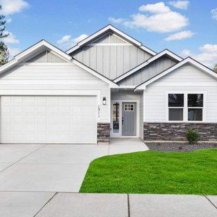 Пример оригинального дизайна: маленький, одноэтажный, серый частный загородный дом в стиле кантри с комбинированной облицовкой, двускатной крышей, крышей из гибкой черепицы, черной крышей и отделкой планкеном