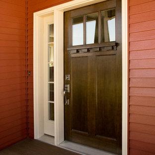 Inredning av en amerikansk mellanstor ingång och ytterdörr, med röda väggar, mörkt trägolv, en enkeldörr och mörk trädörr