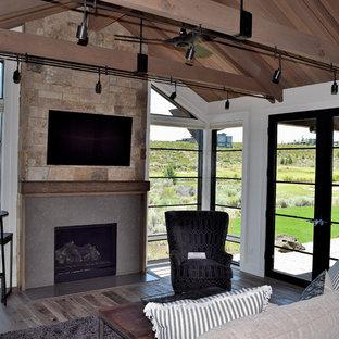 Inspiration pour une salle de séjour rustique de taille moyenne et ouverte avec un mur blanc, un sol en bois brun, une cheminée standard, un manteau de cheminée en pierre, un téléviseur fixé au mur et un sol marron.