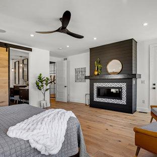 Стильный дизайн: большая хозяйская спальня в стиле модернизм с белыми стенами, светлым паркетным полом, стандартным камином, фасадом камина из вагонки и коричневым полом - последний тренд