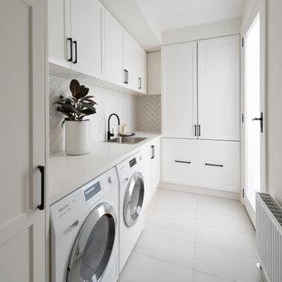 Inspiration för en stor vintage vita linjär vitt tvättstuga, med en nedsänkt diskho, luckor med upphöjd panel, vita skåp, bänkskiva i kvarts, vitt stänkskydd, stänkskydd i stickkakel, mellanmörkt trägolv och brunt golv