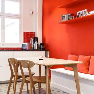 Geschlossene, Große Moderne Küche in L-Form mit Unterbauwaschbecken, flächenbündigen Schrankfronten, weißen Schränken, Granit-Arbeitsplatte, Küchenrückwand in Rot, Rückwand aus Terrakottafliesen, Küchengeräten aus Edelstahl, Keramikboden, Kücheninsel, buntem Boden und schwarzer Arbeitsplatte in Sonstige