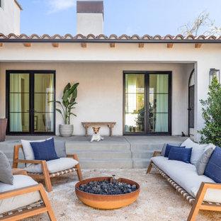 Foto di un grande patio o portico mediterraneo in cortile con un focolare, ghiaia e nessuna copertura