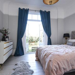 Ejemplo de dormitorio machihembrado y principal, de tamaño medio, con paredes grises, suelo de madera en tonos medios, todas las chimeneas y suelo gris