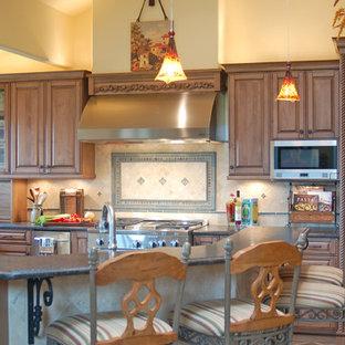 サンルイスオビスポの大きい地中海スタイルのおしゃれなキッチン (レイズドパネル扉のキャビネット、ヴィンテージ仕上げキャビネット、タイルカウンター、緑のキッチンパネル、石タイルのキッチンパネル、パネルと同色の調理設備、スレートの床) の写真