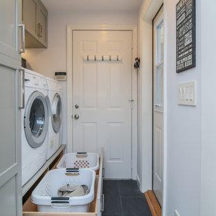 Imagen de lavadero lineal, clásico renovado, con puertas de armario grises, paredes grises, suelo de baldosas de porcelana, lavadora y secadora juntas y suelo negro
