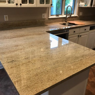 Design ideas for a large u-shaped eat-in kitchen in Other with a double-bowl sink, raised-panel cabinets, white cabinets, granite benchtops, beige splashback, granite splashback, stainless steel appliances, ceramic floors, a peninsula, brown floor and beige benchtop.