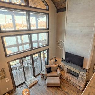 Großes Uriges Arbeitszimmer mit grauer Wandfarbe, braunem Holzboden, Kamin, Kaminumrandung aus gestapelten Steinen, freistehendem Schreibtisch, grauem Boden und Holzdecke in Atlanta
