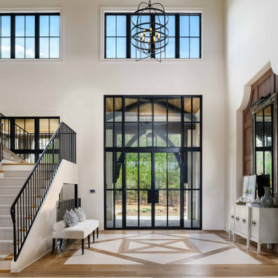 Inspiration for a huge transitional light wood floor, brown floor and wall paneling entryway remodel in Atlanta with white walls and a black front door