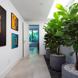 マイアミの広いコンテンポラリースタイルのおしゃれな廊下 (白い壁、磁器タイルの床、グレーの床、クロスの天井) の写真