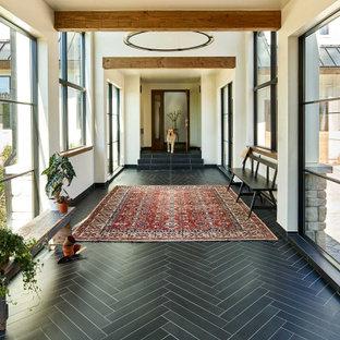 Ispirazione per un grande ingresso o corridoio country con pavimento nero e travi a vista