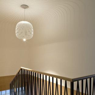 Mittelgroße Retro Holztreppe in U-Form mit Holz-Setzstufen, Stahlgeländer und vertäfelten Wänden in Venedig