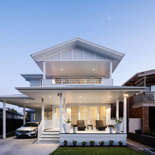 This is an example of a large beach style two-storey white house exterior in Sydney with concrete fiberboard siding, a gable roof, a metal roof, a white roof and board and batten siding.