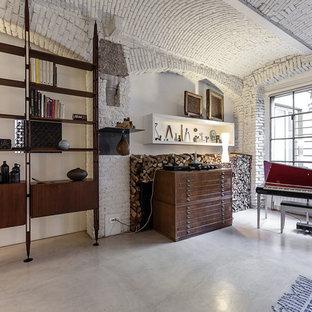 Industriell inredning av ett allrum på loftet, med ett musikrum, vita väggar och betonggolv